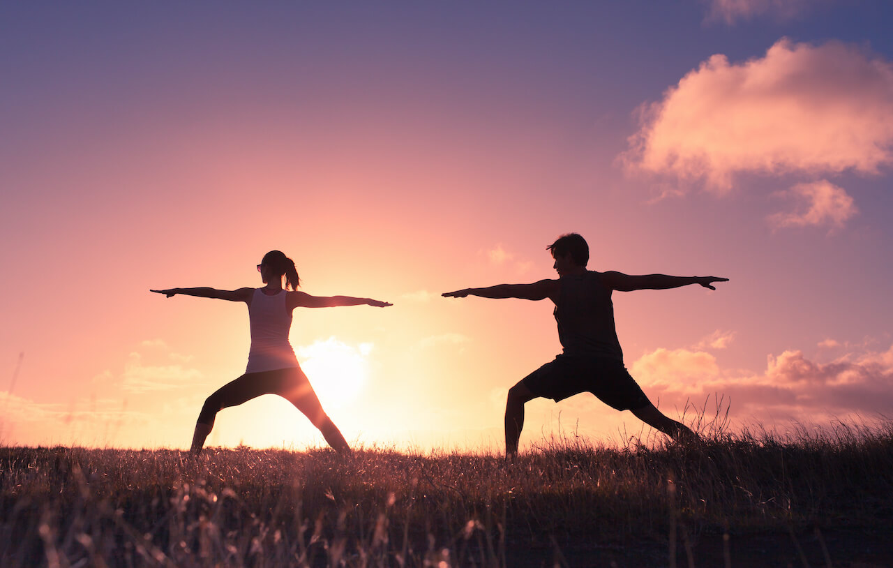 Man and woman practicing yoga stretches at sunset in a open field.